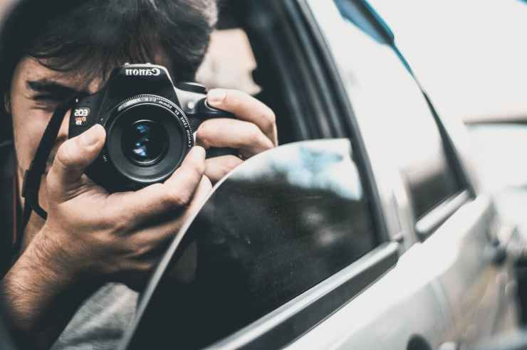 man holding canon camera inside car while capturing a photo