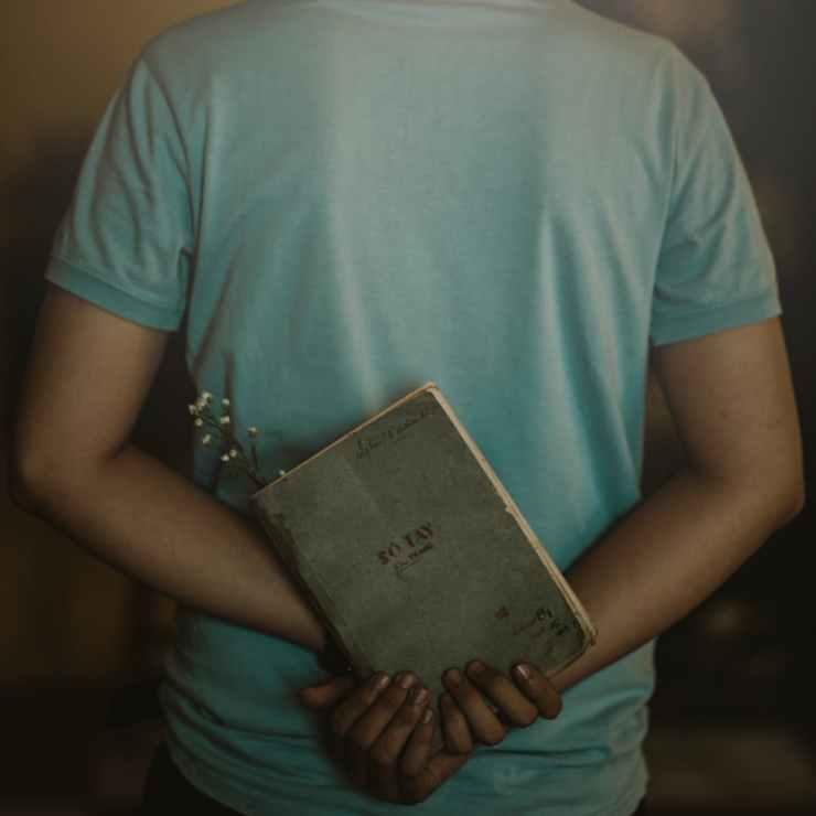 man wearing t shirt holding book