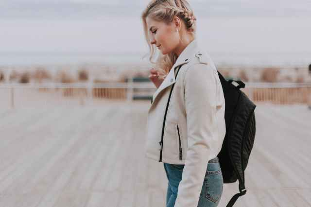 woman in black zip up jacket with black backpack