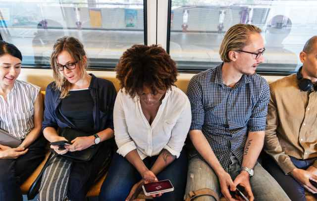 woman sitting holding smartphone between two men and two women