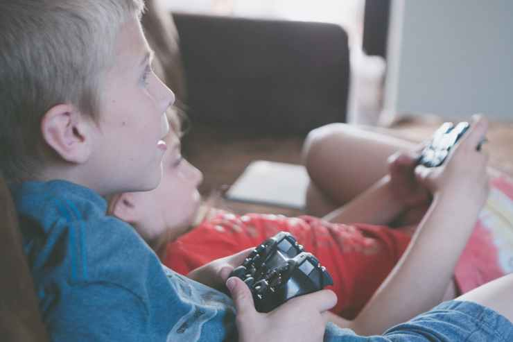 two boy and girl holding game controllers