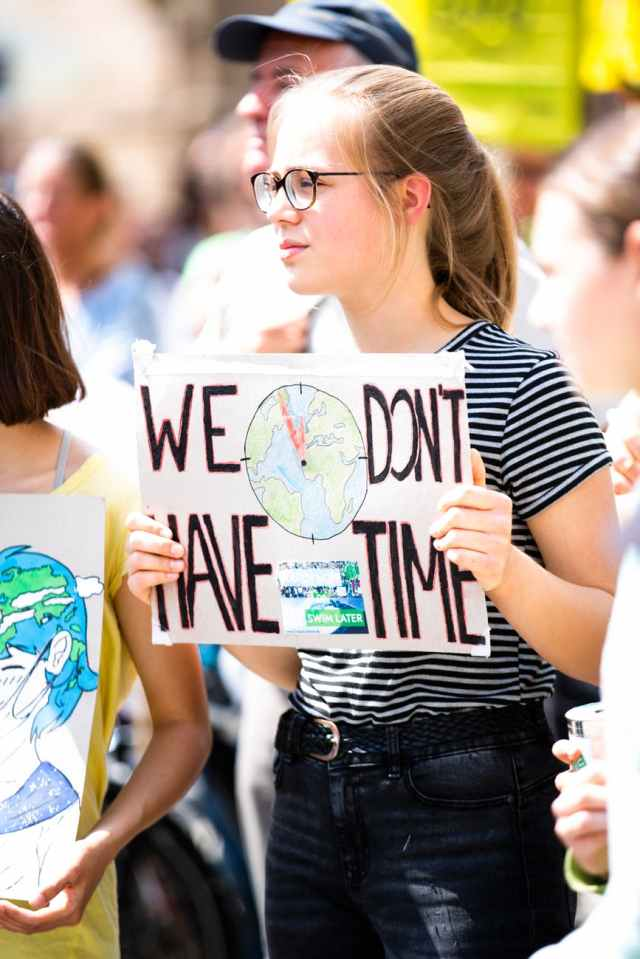 woman holding we don t have time signage