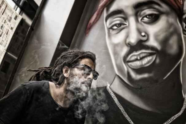 man with dreadlocks and sunglasses poses near tupac shakur portrait