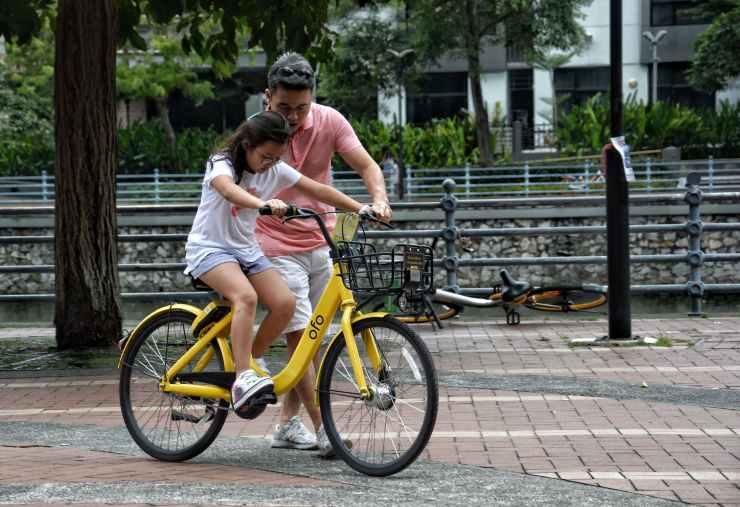 photography of girl riding bike beside man