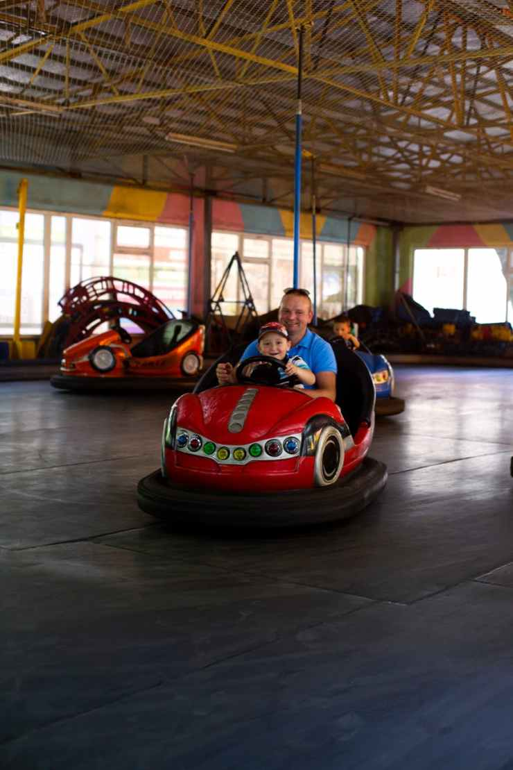 father and child ride bump car at amusement park