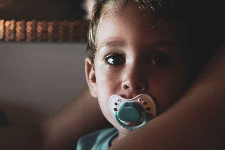 close up photo of boy with pacifier in his mouth