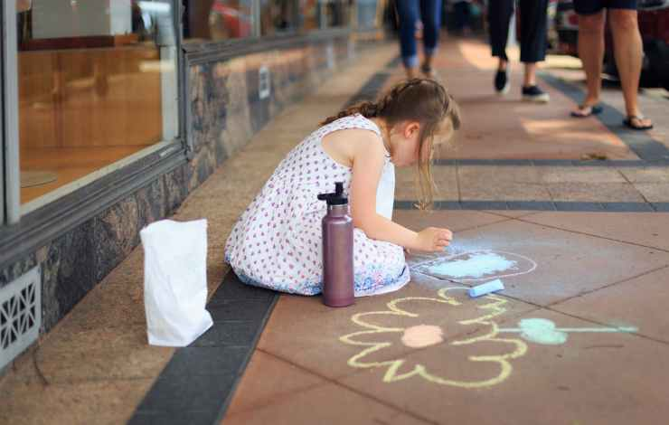 girl drawing on the floor using chalks
