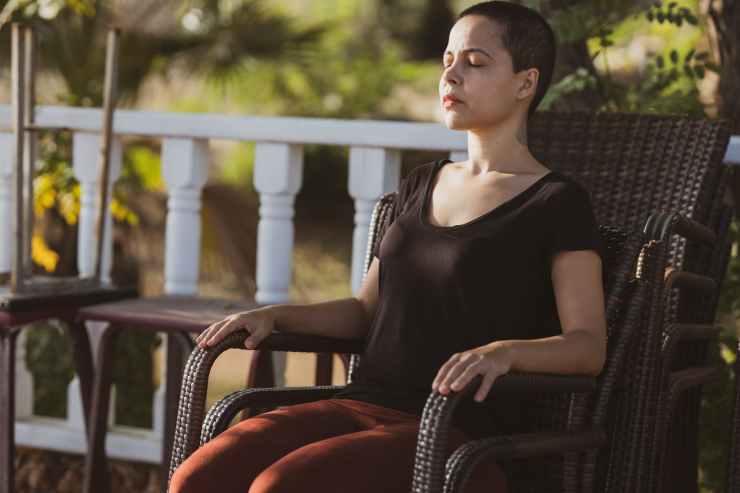 woman in black top sitting on brown armchair