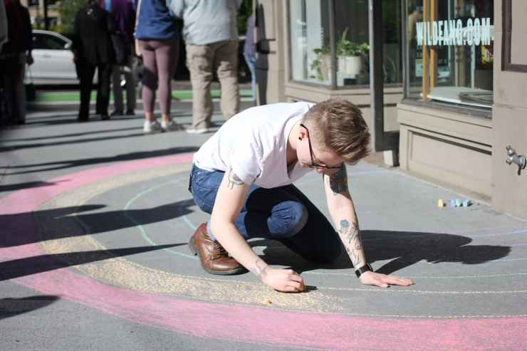 photo of a man in white t shirt coloring on gray pavement next to a building