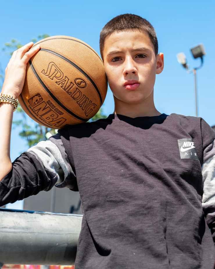 boy holding a basket ball on his shoulder